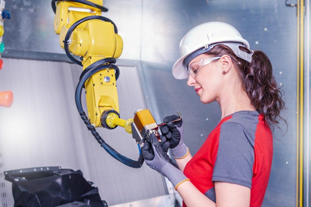 Eine Technikerin arbeitet an einem Roboterarm, der mittels KI gesteuert werden kann